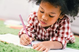 Cute Young African American Kid Girl Drawing Or Painting With Colored Pencil. Kindergarten Children
