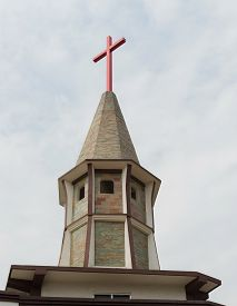 A Red Cross On A Church On An Overcast Day - Upward View