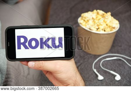 Roku Logo On The Mobile Phone Screen With Popcorn Box And Apple Earpods On The Background. Leisure T