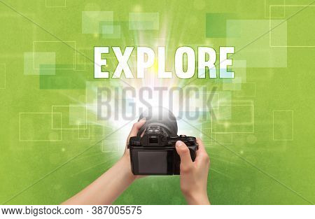 Close-up of a hand holding digital camera with EXPLORE inscription, traveling concept