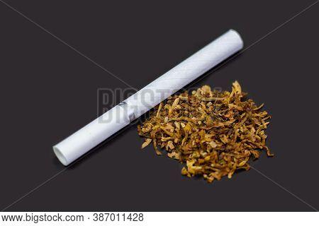 Cigarette And Tobacco On Gray Background. White Cigarette On Gray Table. Dry Tobacco Leaves On Gray