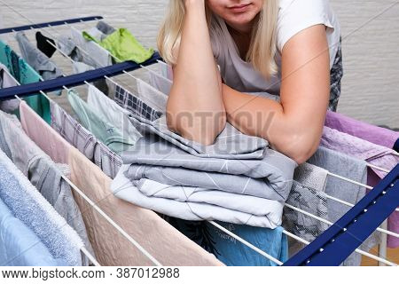 Unrecognizable Woman Collecting Dry Clean Clothes, Linen And Towels From A Drying Rack And Putting I