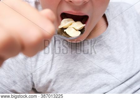 A Hungry Teen Teenager Boy Eating Dumplings Close Up At Home, Convenience And Rapid Cooking Food Con