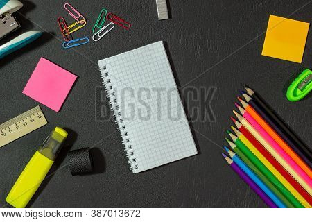 School Supplies And Notepad On A Black Background. Stationery On Chalk Board. Black Textured School