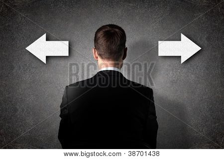 Businessman is standing in front of two direction signs.