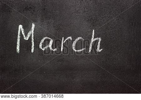 Month Written In White Chalk On A Chalkboard. The Month Depicted On The Chalkboard Is March
