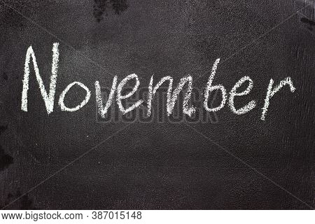 Month Written In White Chalk On A Chalkboard. The Month Depicted On The Chalkboard Is November
