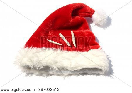 Santa Claus Hat with Marijuana. Isolated on white. Room for text. Marijuana Joints on a Red Santa Hat.