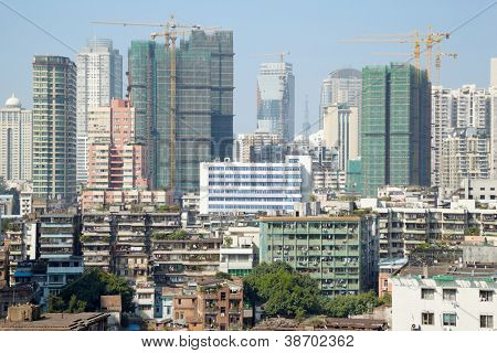 Old houses and new high-rise buildings under construction