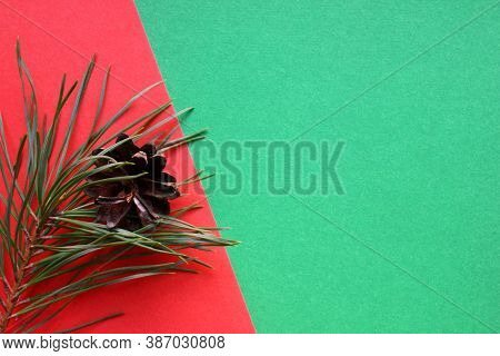 Beautiful Pine Cone And Pine Branches On A Red And Green Background. New Year And Christmas Decorati