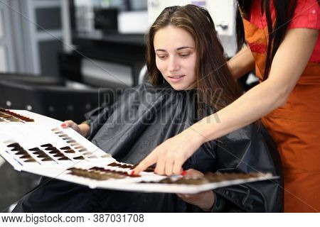 Female Client With Master In Beauty Salon Examines Samples Of Palette Of Hair Dyes. Hair Coloring Of