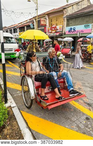 George Town, Penang, Malaysia - December 1, 2019: Classic Local Rickshaw With Tourists In Cloudy Wea