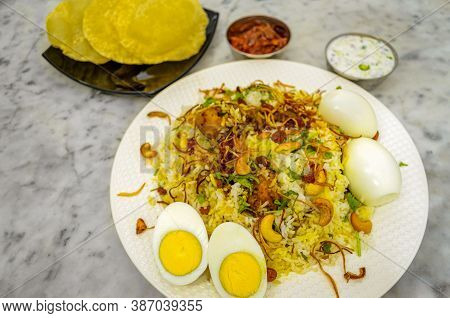 Chicken Biryani With Eggs, Papads, Pickle And Raita On A White Marble Floor - Top View