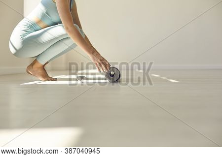 Fit Barefoot Young Female In Activewear Unrolling Rubber Mat Before Yoga Practice In Sunlit Gym