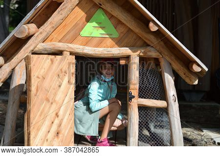 Girl Posing In A Wooden Doghouse On A Hike In The Woods