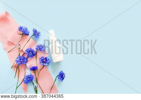 Mock-up Of White Plastic Spray Bottle And Blue Flowers On Light Blue Background. Natural Organic Spa