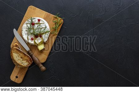 Oven Baked Camembert Cheese With Honey, Figs, And Fresh Bread On A Black Background. Top View, Copy