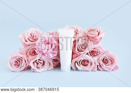 Mockup Of Unbranded White Bottle For Branding And Label And Light Pink Roses On A Pastel Blue Backgr