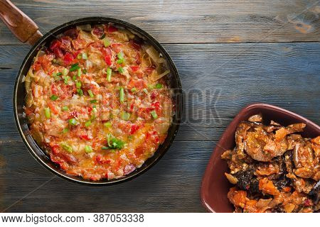 Braised Tomatoes With Onions On Grey Blue Wooden Background. Stewed Tomatoes With Onions In A Metal