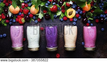 Healthy And Useful Colorful Berry Smoothies With Yogurt, Fresh Fruit And Raw Berries On Brown Backgr