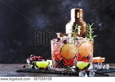 Glasses Of Cranberry Drink Or Cocktail With Rosemary, Cranberries, Vodka And Crushed Ice On Grey Bac