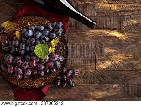 Plate With Purple Grapes And Bottle Of Wine On A Rustic Wooden Table.  Overhead View With Copy Space