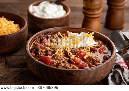 Bowl Of Chili Con Carne With Shredded Cheddar Cheese And Sour Cream On A Rustic Wooden Table