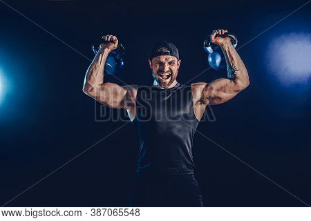 Aggressive Bearded Muscular Bodybuilder Doing Exercise For The Shoulder Muscles, Deltoid With Kettle