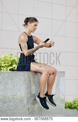 Female Jogger Sitting On Parapet And Checking Pulse Tracker On Her Wrist