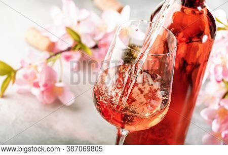 Rose Wine Pouring Out Of The Bottle, Gray Bakcground, Pink Flowers. Rosado, Rosato Or Blush Wine Tas