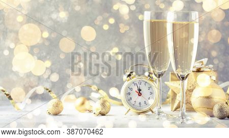 Two Champagne Glasses And Christmas Decoration Over Gray Golden Bokeh Background. Happy New Year Cel