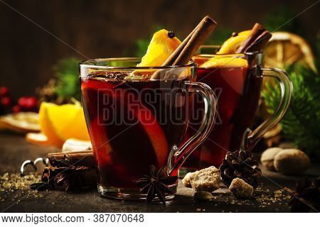 Xmas Hot Mulled Red Wine With Spices And Orange On Wooden Rustic Table. Traditional Christmas Or New