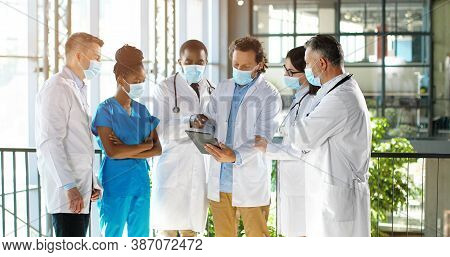 Male Head Of Clinic Standing With Team Of Mixed-races Doctors Colleagues And Using Tablet Device Whi