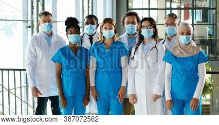 Mixed-races Busy Team Of Male And Female Doctors Posing To Camera And Crossing Hands In Hospital. In