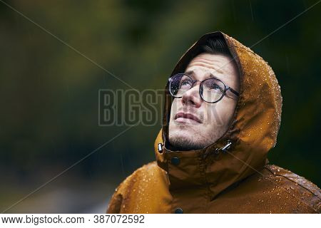 Heavy Rain During Autumn Day. Portrait Of Young Man In Waterproof Jacket.