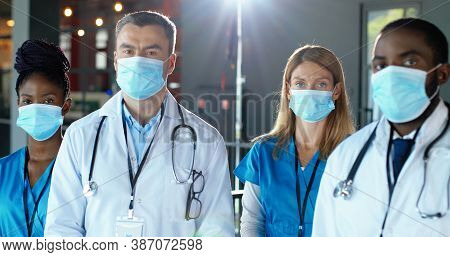 Mixed-races Specialists, Males And Females Doctors In Hospital. International Medics In Medical Mask