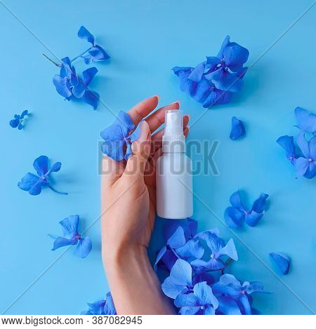 Top View And Close-up Of White Plastic Spray Bottle Mockup, Female Hand And Blue Flowers On A Blue B