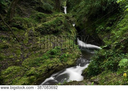 Beautiful Small Narrow Waterfall In Magic Forest. Tiny Waterfall. Long-exposure Photo Of Poulanass W