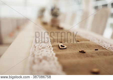 Detail Of Decorated Dining Table With Burlap Tablecloth And White Decorative Lace. On Tablecloth Are