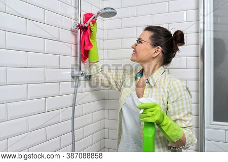 Woman In Gloves With Detergent And Rag Doing Bathroom Cleaning, Washing And Polishing Shower Mixer S