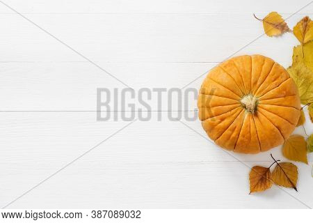 Top View Of Orange / Yellow Pumpkin And Autumn Yellow Leaves On A Shabby White Board Wooden Backgrou
