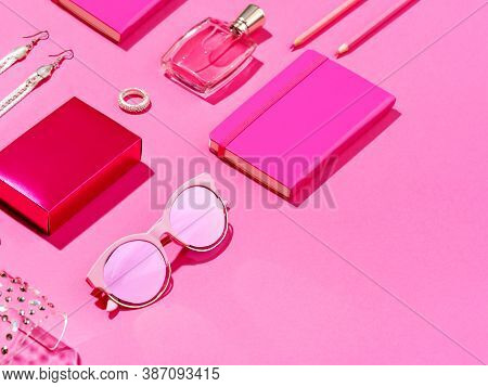 Monochromatic Minimalist Set Of Feminine Accessories. High Angle View Of Pink Notepad, Pencils, Perf