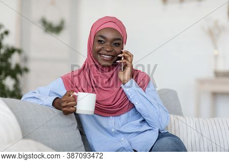 Free Time Leisure. Smiling Young Black Muslim Woman In Hijab Talking On Phone And Drinking Coffee Wh