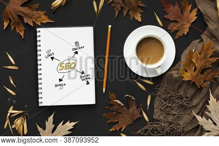 Seo-optimization. Opened Notebook With Seo Scheme Lying On Black Desk Background With Autumn Leaves.
