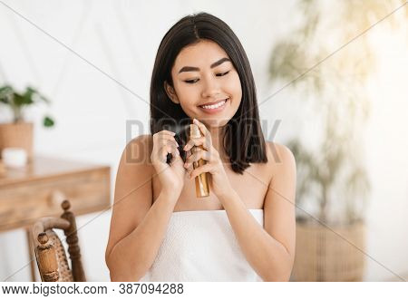 Pretty Happy Asian Woman Applying Hair Oil To Prevent Split Ends, Hair Care At Home Concept, Copy Sp