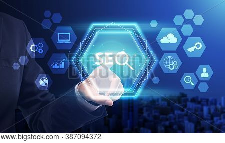 Unrecognizable Businessman Pressing Word Seo Button On Invisible Digital Screen On Blue Background.