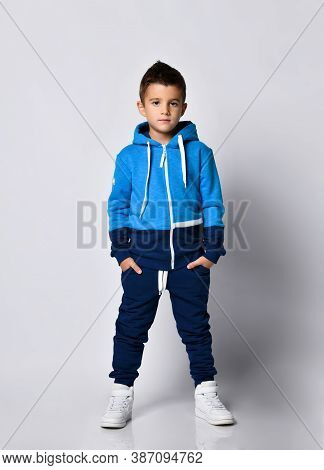 Little Boy Model Wearing Sports Tracksuit With Sweatshirt And Pants Studio Portrait Isolated On Gray