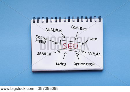 Seo Concept. Opened Notepad With Seo-optimization Scheme With Words Lying Over Blue Background. Web