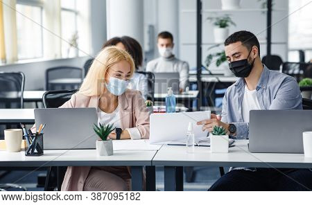 Social Distance And Work With Documents In Modern Office. Millennial Man And Woman In Protective Mas