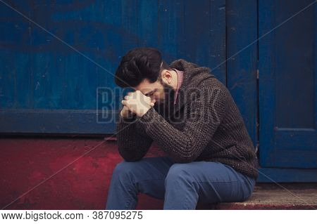Stressed And Upset Young Man Sitting Outside Holding Head With A Hand Looking Down. Human Emotion Fe